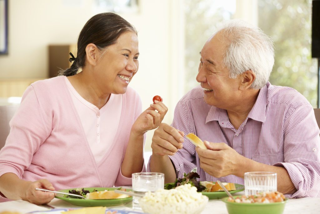 Older Asian couple eating with no problems because of custom dentures from the menu or restorative dentistry services found at Legacy Dental in Omaha, NE.