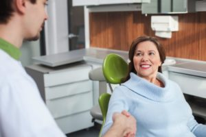 Woman shaking hands with her dentist because the sedation dentistry provided by Legacy Dental relieved her of any anxiety during her visit.