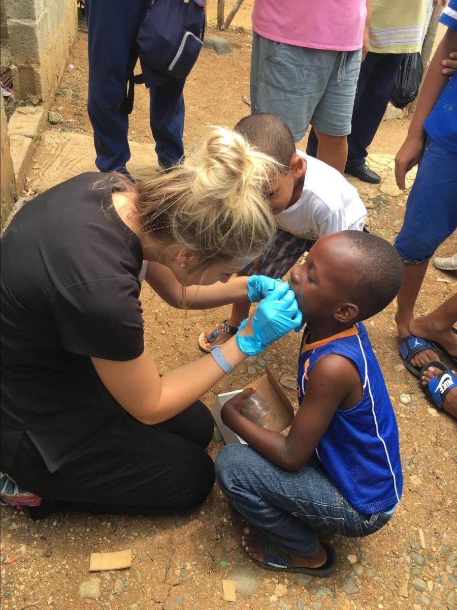 Dr. Maggie Larsen checking a child's teeth in the Dominican Republic